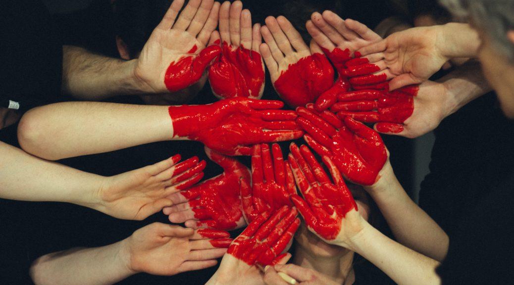 Viele Hände bilden ein rot gemaltes Herz das für Liebe aus dem Team steht